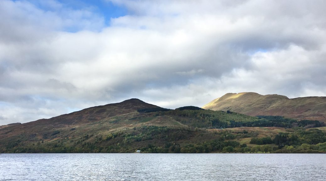 View across Loch Venachar to the Venachar Lochside café against backdrop of Ben Ledi